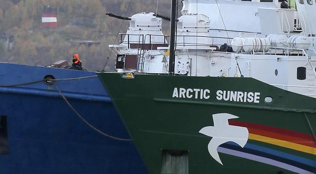 The Greenpeace ship is watched in port by a Russian coast guard vessel (AP)