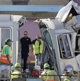 Authorities inspect the wreckage of two Chicago Transit Authority trains that crashed on Monday (AP)