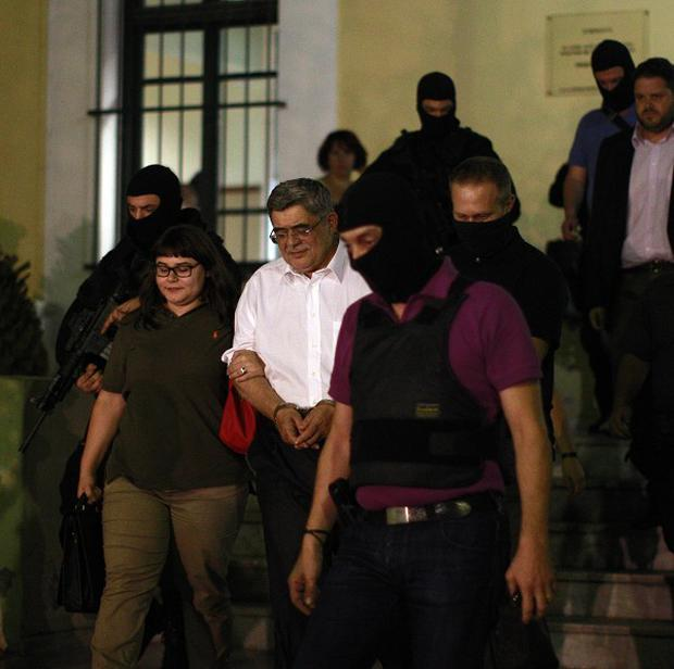 Golden Dawn party leader Nikos Michaloliakos exits a court room in Athens (AP)