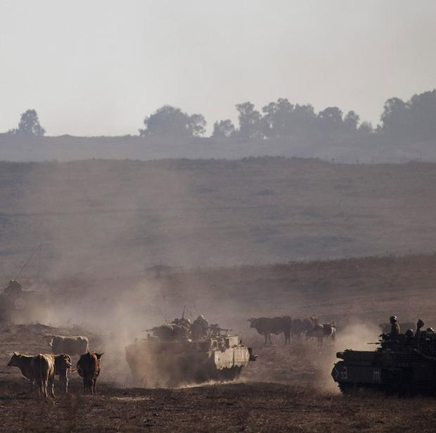 Israeli soldiers drive armored personal carriers during a military exercise in the Israeli-controlled Golan Heights near the border with Syria (AP)