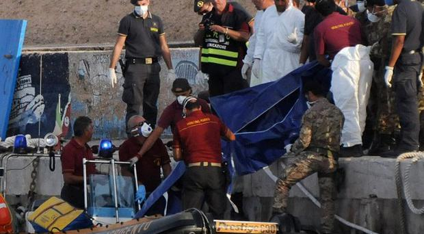 Rescuers lift a body bag as they reach the port of Lampedusa, after a boat carrying hundreds of migrants sank (AP)