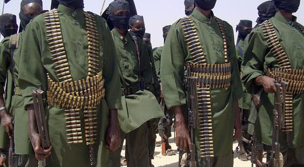 Al-Shabab fighters stand in formation with their weapons during military exercises on the outskirts of Mogadishu, Somalia, in 2011 (AP)