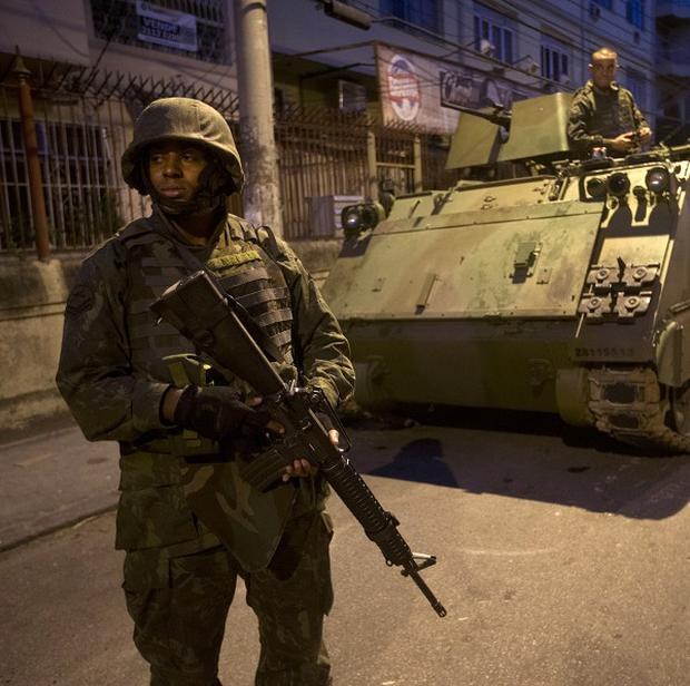 Brazilian soldiers patrol the Lins slum complex during an operation to install a Pacifying Police Unit in Rio de Janeiro (AP)