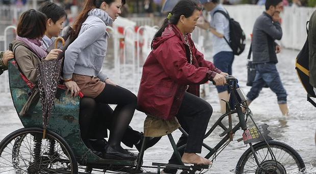 Commuters on a tricycle cross a flooded road outside a subway station in Shanghai, China (AP)