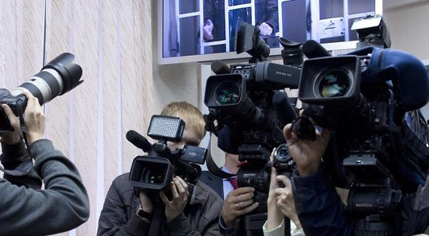 Members of the media take pictures in a courtroom, with Greenpeace freelance photographer Denis Sinyakov shown behind bars on a court video screen in Murmansk (Dmitri Sharomov, Greenpeace/AP)