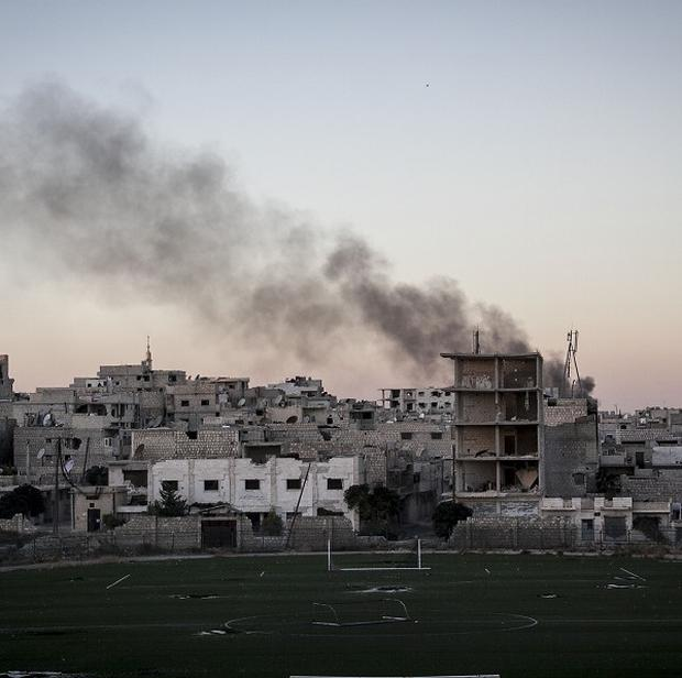 Smoke rises after a mortar shell hits a residential area during fighting between Syrian government forces and rebels in Maaret al-Numan in Idlib province (AP)