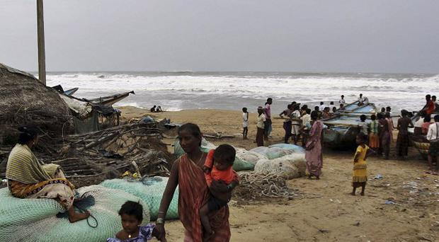 An Indian woman evacuates from the coast with her children as other villagers look at the Bay of Bengal (AP)