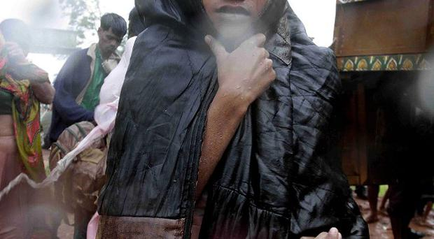 A boy reaches a relief camp after being evacuated as it rains near Berhampur, India, as cyclone Phailin reached land (AP/Bikas Das)