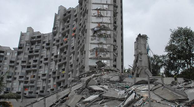 Rescue workers look at the remains of a building that collapsed in Medellin (AP)