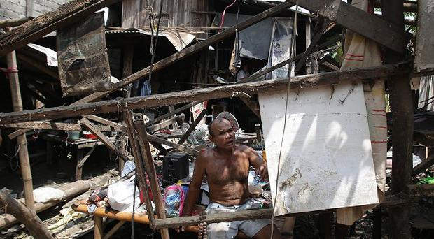 A Filipino inside his damaged house after Typhoon Nari hit northern Philippines (AP)