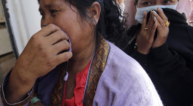 Relatives of a victim of Wednesday's plane crash cry at a Chinese temple in Pakse, Laos (AP)
