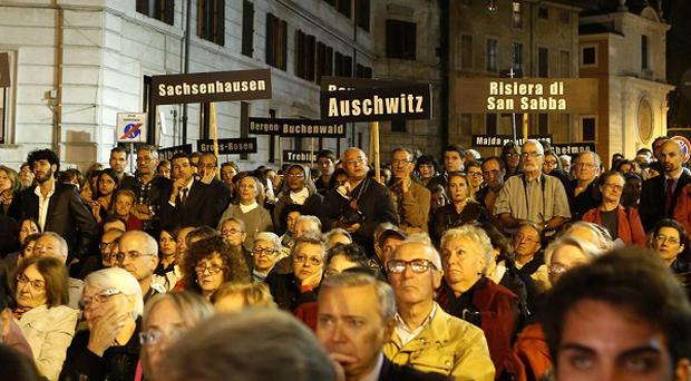 People hold up signs with names of Nazi concentration camps during a march marking the 70th anniversary of the roundup and deportation of Rome's Jews (AP)