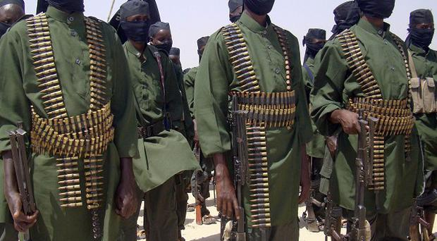 Al Shabab fighters stand in formation with their weapons during military exercises on the outskirts of Mogadishu (AP)