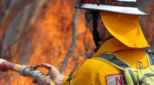 A firefighter battles a blaze burning in the Sydney suburb of Pittwater (AP)