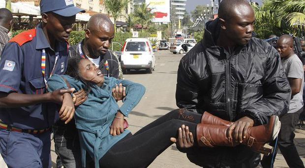 A security officer helps a wounded woman outside the Westgate Mall in Nairobi, Kenya after gunmen threw grenades and opened fire in a terrorist attack (AP)