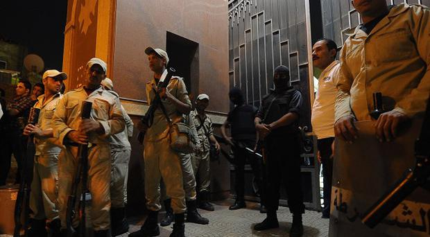 Egyptian security forces stand guard at a Coptic Christian church in the Waraa neighborhood of Cairo after gunmen on motorcycles opened fire (AP)