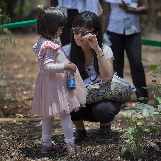 Relatives of one of the mall attack victims with a tree planted in memory (AP)