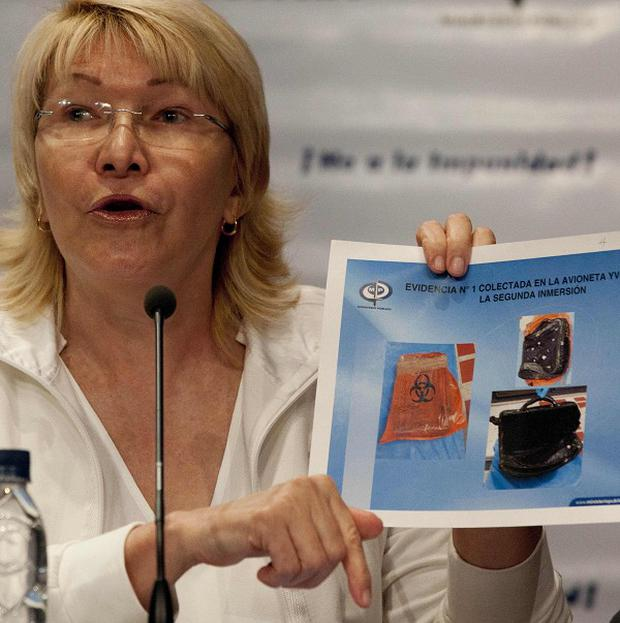 Attorney General Luisa Ortega holds an image showing evidence recovered from the plane that crashed in January in the Los Roques islands during a press conference in Caracas, Venezuela (AP/Ariana Cubillos)