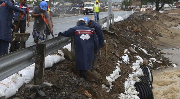 Workers reinforce a road with sandbags in Acapulco, preparing for Hurricane Raymond (AP)