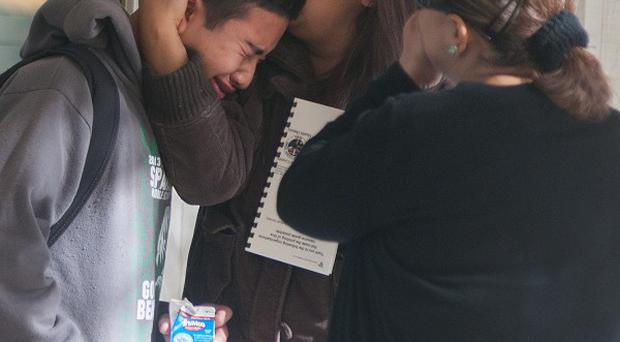 A Sparks pupil is comforted after a student killed a teacher and wounded two boys in a gun rampage.