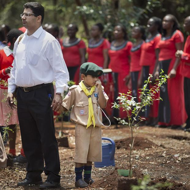 Khalil Rashid, six, holds his father's hand as he waits to plant a tree in memory of his schoolmate Jennah Bawa, eight, who was shot with her mother Zahira, in the Westgate Mall terrorist attack (AP)