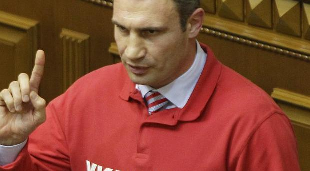 Chairman of the Ukrainian opposition party Udar (Punch) and WBC Heavyweight Champion boxer Vitali Klitschko, speaks to lawmakers in Kiev, Ukraine, Thursday, Oct. 24, 2013. Klichko announced Thursday that he would run for President in 2015. The words emblazoned on the shirts read, 'Ukraine is Europe'.(AP Photo/Sergei Chuzavkov)