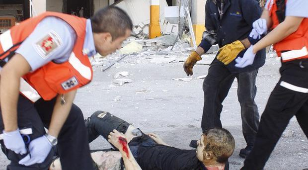 Rescue workers help an injured man after an explosion at a confectionery factory in Ciudad Juarez, Mexico.