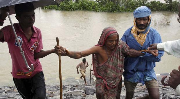 Indian villagers help an elderly woman to safer ground after crossing floodwaters in Khurda district, in the eastern Indian state of Orissa.