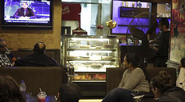 Egyptians watch satirist Bassem Youssef on TV at a coffee shop in Cairo.