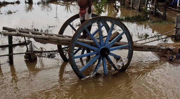 A villager stands on a cart outside his flooded home at Purushatampur in Ganjam district of Orissa state, India.