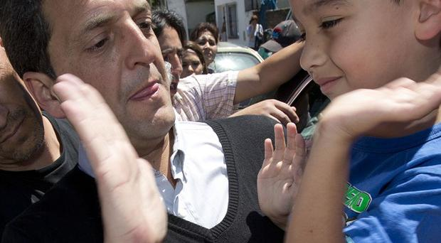 Leading opposition candidate Sergio Massa holds a child in his arms after casting his vote.