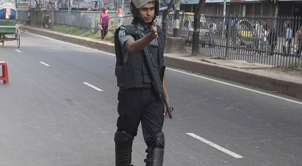 A Bangladeshi police official signals to a driver to stop a vehicle for a security check on the last day of a three-day general strike by the opposition parties in Dhaka (AP)