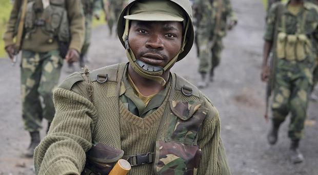 Congolese army soldiers march into Kibumba town after recapturing it from M23 rebels over the weekend (AP)