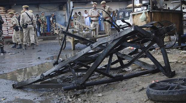 Indian security personnel stand at the site where a crude bomb exploded near the Khwairamband market in Imphal (AP)