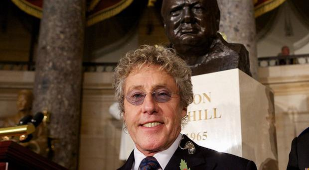 The Who's Roger Daltrey poses in front of a bust of Winston Churchill in Statuary Hall on Capitol Hill in Washington, Wednesday, Oct. 30, 2013, before a ceremony to dedicate the bust. Senate and House leaders, as well as Secretary of State John Kerry, gathered on Wednesday to dedicate the Churchill bust, which will now stand in the Capitol as a testament to the strength of the relationship between the US and the United Kingdom. (AP Photo/Molly Riley)