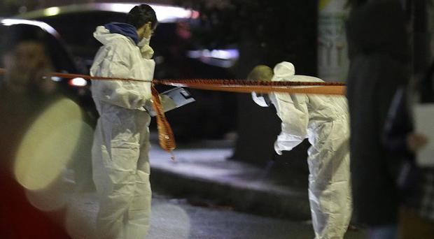 Police investigate the area around an office of the Golden Dawn party in northern Athens
