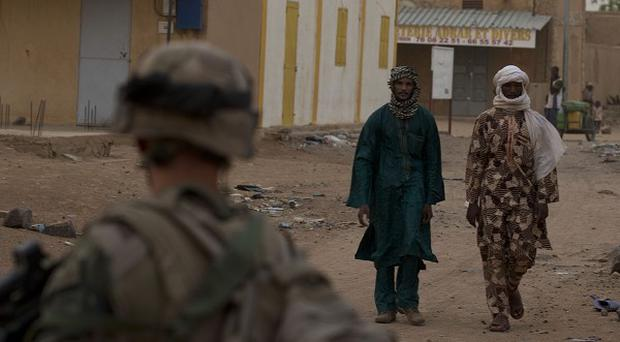 A French soldier patrols at dusk in a central market in Kidal, Mali (AP)