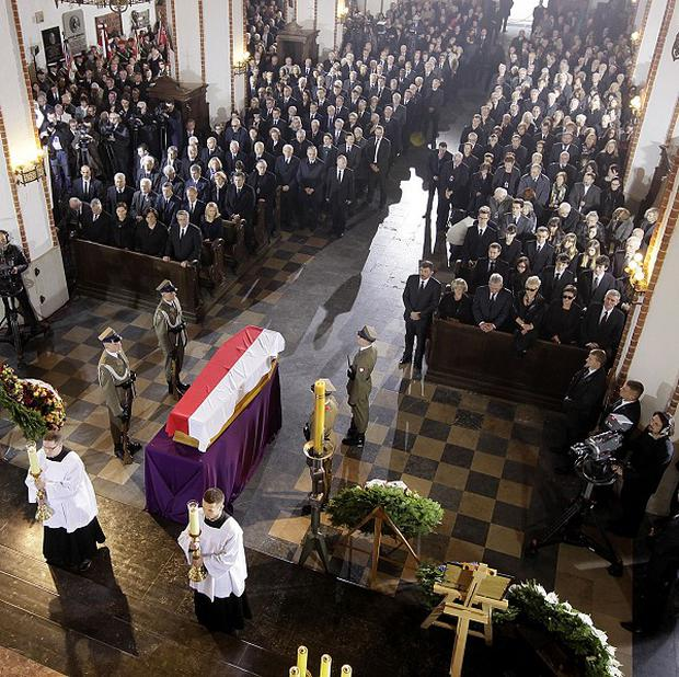 The coffin of Poland's first post-communist prime minister, Tadeusz Mazowiecki, covered with the national flag lying in state at St.Johns Arch Cathedral during a funeral Mass in Warsaw today.