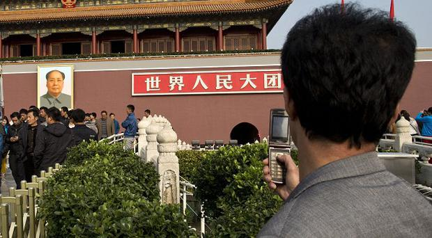 A tourist takes photos of the scene where a vehicle crashed and caught fire near Tiananmen Square. A leading general has been replaced, in a move that appears to be linked to the incident.