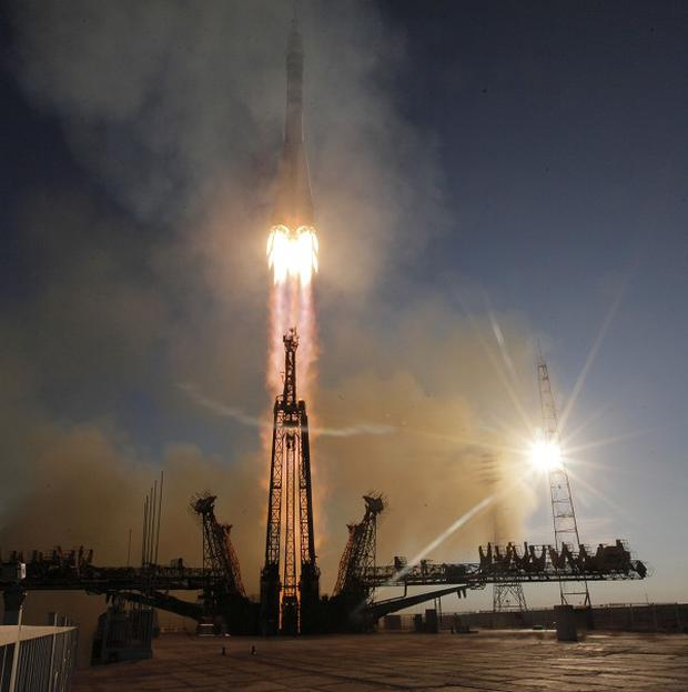 The rocket carrying three astronauts and the Olympic torch blasted off from the Baikonur cosmodrome in Kazakhstan on Thursday
