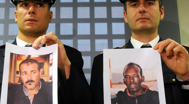 Two Italian policemen hold pictures of Palestinian Attour Abdalmenem, left, and Somali Mouhamud Elmi Muhidin who have been arrested over the migrant shipwreck disaster (AP)