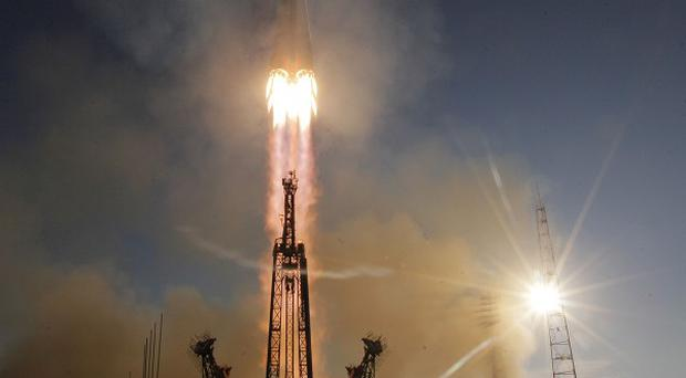 The rocket carrying three astronauts and the Olympic torch blasted off from the Baikonur cosmodrome in Kazakhstan on Thursday (AP)