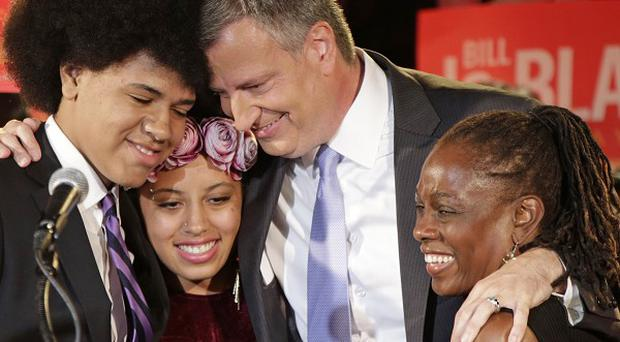 New York mayor-elect Bill de Blasio hugs son Dante and daughter Chiara, left, and wife Chirlane McCray on election night.