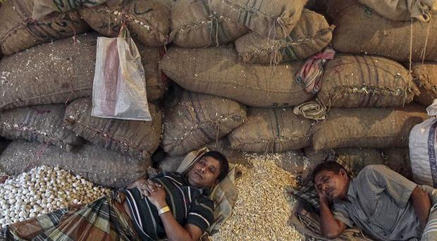Bangladeshi shopkeepers sleep at a wholesale market on the second day of a four-day general strike in Dhaka (AP)