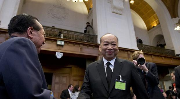 The Cambodian and Thai foreign ministers greet each other in the court (AP)