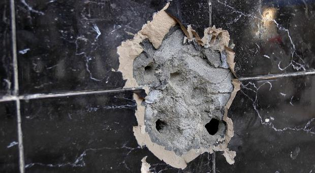 The a bullet-riddled wall of an Afghan bakery where Nasiruddin Haqqani was assassinated (AP)