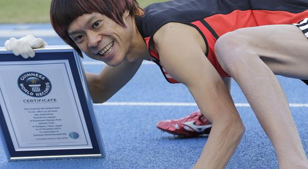 Kenichi Ito with a Guinness World Records certificate after setting the fastest time for the 100-metre dash on his arms and legs in Tokyo. (AP)