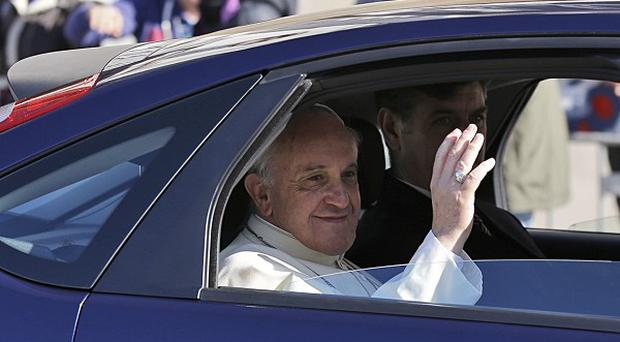 Pope Francis blesses the faithful from the backseat of his car as he leaves the Quirinale Presidential palace (AP)