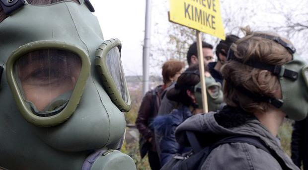 People wearing gas masks protest in front of the Albanian Embassy in Skopje, Macedonia, over plans to destroy Syrian chemical weapons in nearby Albania. (AP)