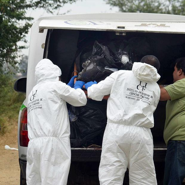 Forensic investigators with a body that was recovered from a mass grave in La Barca, Mexico